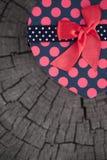 Forma del cuore del contenitore di regalo sul tronco di legno Fotografia Stock