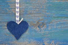 Forma del cuore del denim contro superficie di legno blu nella f stile country Immagini Stock