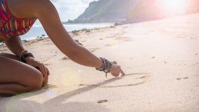 Forma del cuore del disegno della giovane donna in sabbia sulla spiaggia, Bali Immagini Stock Libere da Diritti