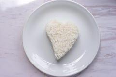 Forma del cuore del riso sul piatto bianco Fotografia Stock