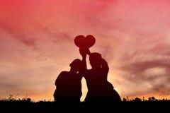 Forma del cuore della tenuta della madre e del figlio della siluetta fotografia stock