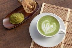 Forma del cuore di arte del latte di Matcha sulla cima sulla tavola di legno con un certo gr Immagine Stock