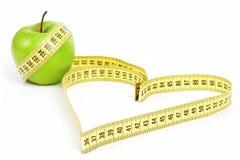 Forma del cuore di misura di nastro e mela verde Fotografie Stock