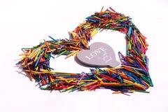 Forma del cuore di Multicoress con lo slogan circa amore immagini stock libere da diritti