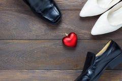 Forma del cuore di vista superiore con le scarpe del ` s delle scarpe e delle donne del ` s degli uomini su legno Immagine Stock