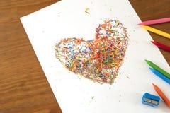 Forma del cuore fatta con i resti delle pitture della cera nei colori luminosi Fotografia Stock