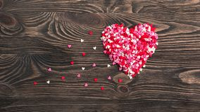 Forma del cuore fatta di piccoli cuori su un fondo di legno Immagine Stock