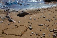 Forma del cuore nella sabbia vicino vedere fotografia stock