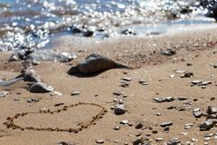 Forma del cuore nella sabbia vicino vedere fotografia stock libera da diritti