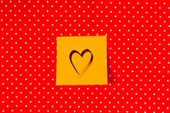 Forma del cuore scritta sulla nota appiccicosa sul fondo rosso del pois fotografia stock libera da diritti