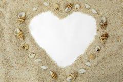 Forma del cuore sulla sabbia con le conchiglie fotografia stock