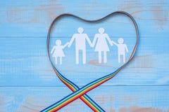 Forma del papel de la gente con la cinta del arco iris de la forma del corazón de LGBTQ en el fondo de madera en colores pastel a fotografía de archivo