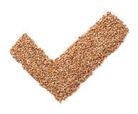 Forma del segno di spunta fatta dei semi del grano saraceno Fotografia Stock