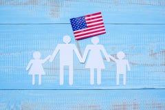 Forma della carta della famiglia o della gente con la bandiera degli Stati Uniti d'America su fondo di legno blu Festa di U.S.A.  fotografie stock libere da diritti