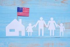 Forma di carta domestica della gente o del famiglia e con la bandiera degli Stati Uniti d'America su fondo di legno blu Festa di  fotografie stock