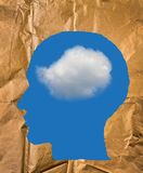 A forma di di carta sgualcito come una testa umana, un cielo blu e nuvola bianca Immagine Stock Libera da Diritti