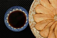 Forma di color salmone del fiore della griglia del sashimi sul piatto del cerchio su giusto fondo nero Immagini Stock Libere da Diritti