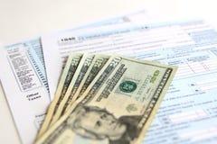 Forma 1040 di imposta di U.S.A. con 20 fatture di dollaro americano Fotografia Stock Libera da Diritti