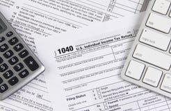Forma di imposta federale 1040 con la tastiera ed il calcolatore Fotografie Stock