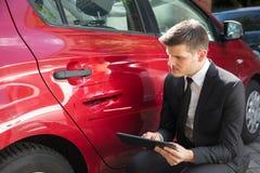 Forma di riempimento di assicurazione dell'uomo vicino all'automobile nociva immagini stock libere da diritti
