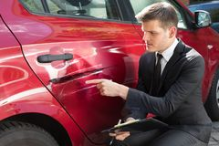 Forma di riempimento di assicurazione dell'uomo vicino all'automobile nociva fotografie stock libere da diritti