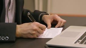 Forma di riempimento del contratto della mano dell'uomo d'affari con la penna video d archivio