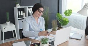Forma di riempimento della donna di affari facendo uso del computer portatile all'ufficio video d archivio