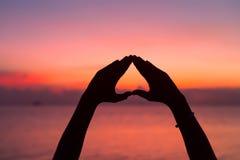 Forma do coração com mãos no fundo do por do sol Imagens de Stock Royalty Free