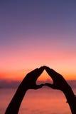 Forma do coração com mãos no fundo do por do sol Fotografia de Stock