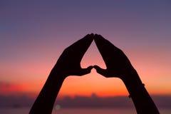 Forma do coração com mãos no fundo do por do sol Fotos de Stock Royalty Free