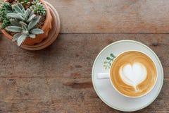 Forma do coração da espuma do leite do café do latte da arte da vista superior com o cacto em w Fotografia de Stock Royalty Free