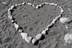 Forma do coração das pedras na areia preta fotografia de stock royalty free
