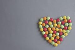 Forma do coração das tabuletas multi-coloridas das drageias em um fundo tecido cinzento Imagens de Stock