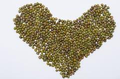Forma do coração do feijão de Mung na tabela branca Fotografia de Stock Royalty Free