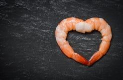 Forma do coração dos camarões do marisco dois/camarões cozinhados do camarão no fundo escuro fotografia de stock