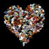 Forma do coração feita das pedras semi preciosas misturadas isoladas em Bla imagens de stock