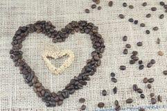 Forma do coração feita inteiramente fora dos grãos de café colocados em um coffe Imagem de Stock Royalty Free
