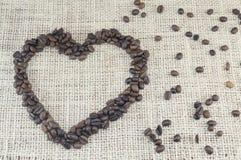 Forma do coração feita inteiramente fora dos grãos de café colocados em um coffe Imagens de Stock Royalty Free