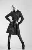 Forma do estúdio disparada: menina bonita no revestimento e em botas pretos. Preto e branco Foto de Stock Royalty Free