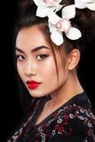 A forma do estúdio disparou da mulher asiática com a flor branca no cabelo fotografia de stock