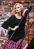 Forma do Grunge: jovem mulher bonito na saia quadriculado e no revestimento que estão na escada fotos de stock