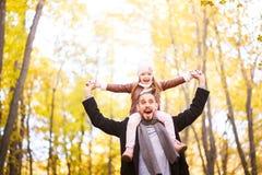 Forma do outono para crianças e a família inteira Uma filha pequena senta-se nos ombros do pai no pescoço contra o CCB fotografia de stock