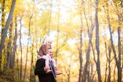 Forma do outono para crianças e a família inteira Uma filha pequena senta-se nos ombros do pai no pescoço contra o CCB imagens de stock royalty free