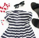 Forma do verão, equipamento do verão no fundo branco Vestido listrado azul, sandálias pretas, óculos de sol pretos, colar vermelh foto de stock