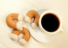 Forma em ferradura dos biscoitos do gengibre com xícara de café branca Fotos de Stock Royalty Free