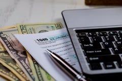 Forma federal 1040 del impuesto con el teclado de ordenador y los dólares americanos fotografía de archivo libre de regalías