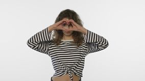 Forma feliz del corazón de la demostración de la muchacha en el fondo blanco Símbolo del corazón de la demostración de la mujer j almacen de video