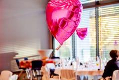 Forma festiva cor-de-rosa dos balões do coração com os convidados do partido no fundo Fotografia de Stock