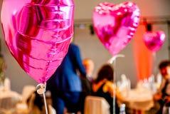 Forma festiva cor-de-rosa dos balões do coração com os convidados do partido no fundo Fotos de Stock