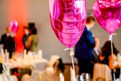 Forma festiva cor-de-rosa dos balões do coração com os convidados do partido no fundo Fotografia de Stock Royalty Free